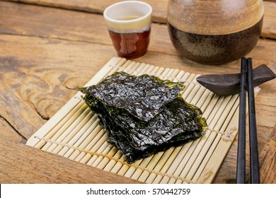 Nori sheets with sticks on the wood background