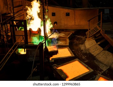 Norilsk, Krasnoyarsk Region, Russia - November 18, 2018: Copper production at the metallurgical plant. The molten metal is poured into large molds for casting. When smelting the evaporation of gases.