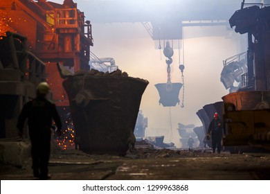 Norilsk, Krasnoyarsk Region, Russia - November 18, 2018: Copper production at the metallurgical plant. Industrial structures, ore buckets, overhead cranes and workers. Fumes due to smelting metal.