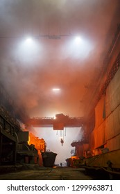 Norilsk, Krasnoyarsk Region, Russia - November 18, 2018: Copper production at the metallurgical plant. Industrial structures, ore buckets, cranes and workers. Flames and fumes due to smelting metal.