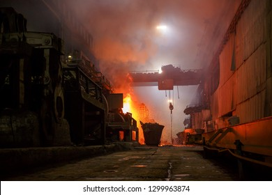 Norilsk, Krasnoyarsk Region, Russia - November 18, 2018: Copper production at the metallurgical plant. Large industrial structures, ore buckets, overhead cranes. Flames and fumes due to smelting metal