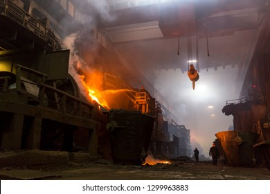 Norilsk, Krasnoyarsk Region, Russia - November 18, 2018: Copper production at the metallurgical plant. A worker from a hose pours lime mortar on the converter with molten metal. Bright flames, fumes.