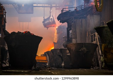 Norilsk, Krasnoyarsk Region, Russia - November 18, 2018: Copper production at the metallurgical plant. Molten metal pours from a huge ore bucket. Large industrial structures, overhead cranes, fumes.