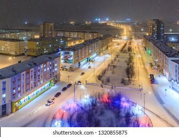 Norilsk, Krasnoyarsk Region, Siberia, Russia - November 17, 2018: Top view of the Krasnoyarsk street. Snowfall on a cold winter evening in the arctic. Colorful street lighting of a large northern city