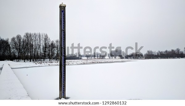 Normaal Amsterdams Peil (NAP), Amsterdam Ordinance Level, a vertical level meter in river landscape. winter scenery