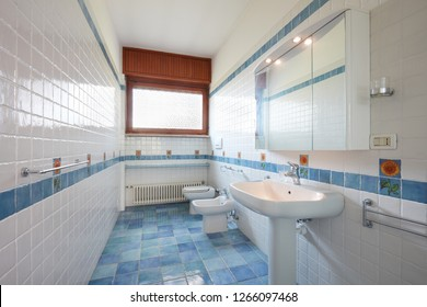 Normal bathroom with blue and white tiles in apartment interior