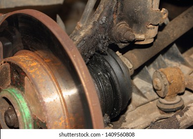 Normal brake disk and destroyed CV joint duster - repair car suspension and gear drive on left side with removed wheel