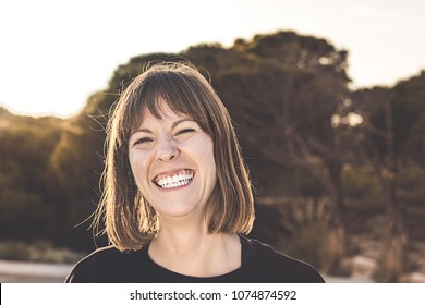 Normal brunette girl smiling. Woman with a smile on a sunset. Happy Expression