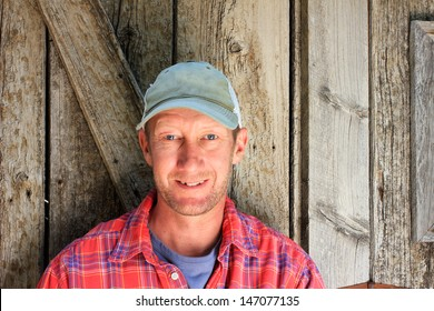 Normal man beside barn wood door with ball cap and plaid shirt.