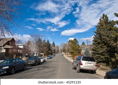 Normal suburban street scene on a peaceful and quiet day with interesting clouds