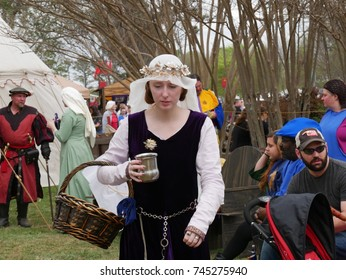 NORMAN, OKLAHOMA—APRIL 2017: A woman wearing a Medieval dress and head veil carry a silver cup and wicker basket at the festival grounds in Norman.