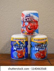Norman, OK June 20, 2018 three different flavors of Kool-Aid drink mixes on a wooden table with a white background.
