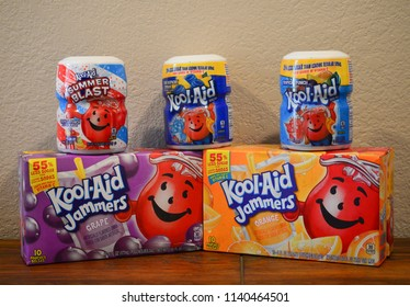 Norman, OK June 20, 2018 Close up photo of a grape and orange Kool-Aid Jammers box and three different flavors of Kool-Aid drink mixes on a wooden table with a white background.
