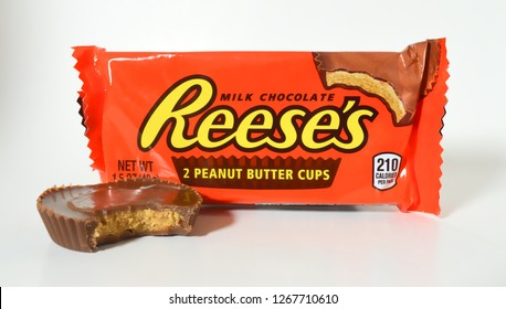 Norman, OK Oct. 31, 2018 A partially eaten Reese's peanut butter cup in front of a package of peanut butter cups with a white background
