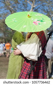 NORMAN, OKLAHOMA -  APRIL 01 2007: A couple with medieval costume hiding under an umbrella in annual Medieval Fair event