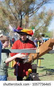NORMAN, OKLAHOMA -  APRIL 01 2007: A man wearing medieval costume with hat and colorful feather teaching a boy using crossbow in annual Medeval Fair event