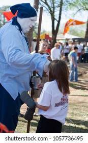 NORMAN, OKLAHOMA -  APRIL 01 2007: A jester performing a trick to a girl in annual Medieval Fair event