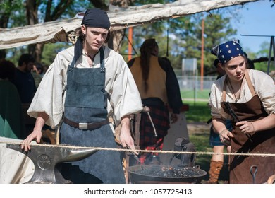 NORMAN, OKLAHOMA -  MARCH 31 2007: A female and a male medieval blacksmith work at their workshop in annual Medieval Fair event