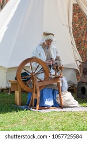 NORMAN, OKLAHOMA -  MARCH 31 2007: A woman wearing white costume sitting on a loom in annual Medieval Fair event