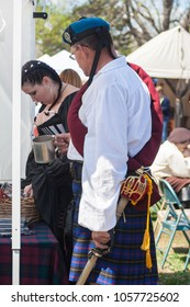NORMAN, OKLAHOMA -  MARCH 31 2007: A man wearing medieval costumes holding a mug and a sword in annual Medieval Fair event
