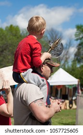 NORMAN, OKLAHOMA -  MARCH 31 2007: A little boy with an axe sitting on his father's neck in annual Medieval Fair event