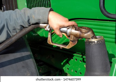Normandy, France, April 2012. Farmer refuelling his tractor with gas-oil