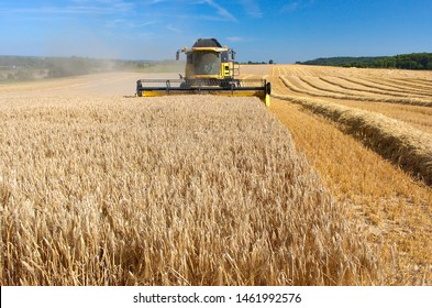 Normandy, France,  August 2007. Barley harvest. Combine harvester in the field. Release grain into a skip with tractor