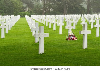 NORMANDY, FRANCE - June 12, 2018: White crosses of fallen soldiers and isolated bouquet of flowers of World War II in American Cemetery.