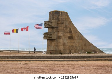 NORMANDY, FRANCE -  June 12, 2018:  War memorial at Omaha beach with American, Canadian, Belgium and Polish flags. An Allied landing beach for D-Day 6 June 1944 Colleville-sur-Mer Normandy, France.