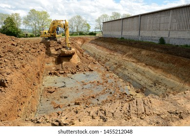 Normandy, France, June 2013. Construction of a liquid manure pit in a dairy farm. Digging of the pit with an excavator