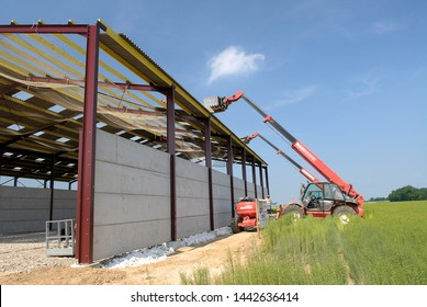 Normandy, France, March 2008. Construction of a new farm building for cows breeding with a steel frame. Roof Sheathing Installation. Roofer on the roof. Installation of safety net as fall prevention