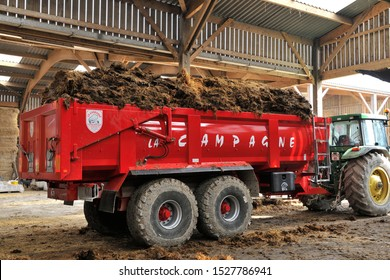 Normandy, France, March 2013. Loading of manure in a stall of dairy farming to be spread in a field