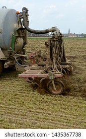 Normandy, France, May 2013. Manure spreading on a meadow with landfill. Tractor and manure tank with drag hose injector for slurry.