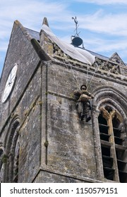 Sainte-Mère-Église, Normandy/France, June 12, 2018: A U.S. paratrooper landed on this village chapel on D-Day. The chapel still has a replica of the trooper hanging on the steeple as a commemoration.