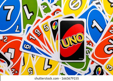 Luleå, Norrbotten/Sweden - February 29, 2020:  Uno card game scattered on a table with a hand of uno cards on top with one reversed. The game was developed in 1971 by Merle Robbins in Reading, Ohio.
