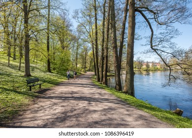 NORRKOPING, SWEDEN - MAY 7, 2018: People enjoy spring atmosphere in the city park along Motala river in Norrkoping, Sweden.  Norrkoping is a historic industrial town in Sweden.