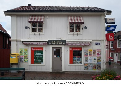 NORRTALJE, SWEDEN - AUGUST 12, 2018: Front view of a white wooden general store with betting and tobacco signs in Norrtalje Sweden August 12, 2018. Town square with nearby buildings.