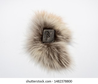 Norse rune Ansuz, isolated on fur and white background. The voice of God. Freedom. Verbal and sound signs. Rune Ansuz is associated with the supreme Scandinavian God Odin.