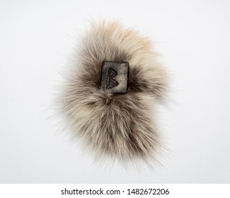 Norse rune Bercana, isolated on fur and white background. Birch, femininity, motherly care and protection. The rune is associated with the Scandinavian Goddess Frigg.