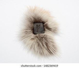 Norse rune Fehu, isolated on fur and white background. Wealth, creativity, passion, fire. Rune Fehu is associated with the Scandinavian goddess Freya.