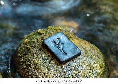 Norse rune Fehu on the stone and the evening river background. Wealth, creativity, passion, fire. Rune Fehu is associated with the Scandinavian goddess Freya, blur