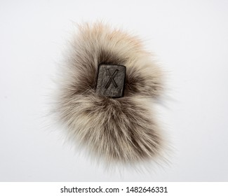 Norse rune Gebo (Gibu), isolated on fur and white background. Gift, balance, harmony, giftedness. The rune is associated with the supreme Scandinavian God Odin.