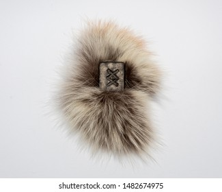 Norse rune Ingwaz, isolated on fur and white background. Seed, potential, energy, fertility. The rune is associated with the Scandinavian god Freyr.