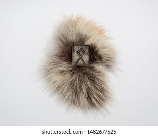 Norse rune Othala (Odal), isolated on fur and white background. Men's maturity, family, home, tradition, property protection. The rune is associated with the supreme Scandinavian God Odin.