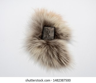 Norse rune Raidho, isolated on fur and white background. Traffic, direction, path, vehicle. The rune of order and legality, it helps in judicial and bureaucratic cases.