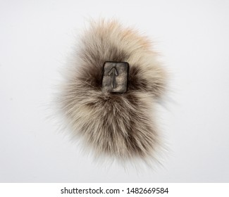 Norse rune Teihwaz (Tihwaz,Tyr), isolated on fur and white background. Law, order, protection, nobility, courage. The rune is associated with the Scandinavian god Tur.