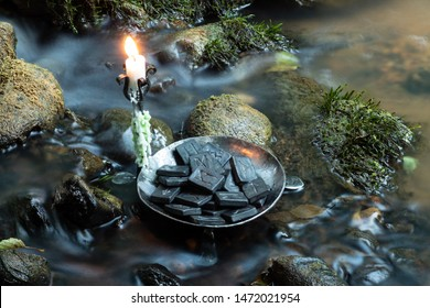 Norse Runes in a forged bowl with candle. In the evening  on the river