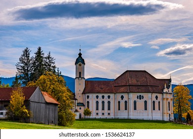 The nortface of the Wieskirche, a beautiful and rich decorated church of pilgrimage in Bavaria, with foehn clouds, green meadows and deciduous trees in autumn