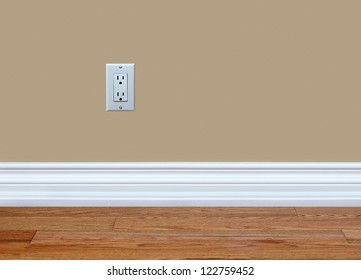 North American 110 volt wall electrical outlet on wall with baseboard and hardwood floor.