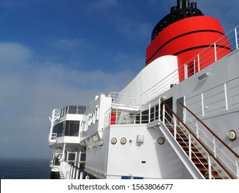 North Atlantic ocean - 29th April 2015:  Queen Victoria cruise ship exterior showing distinctive red funnel against a blue sky and distant mist on horizon. At sea, mid Atlantic inbound to Southampton.